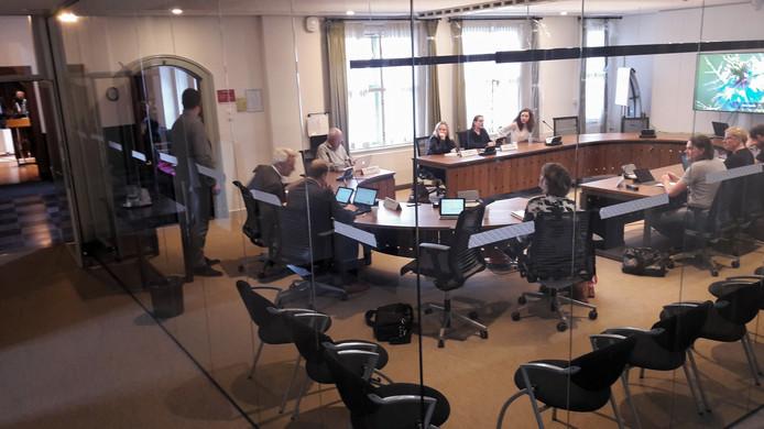 De door een glazen wand omgeven commissiekamer.