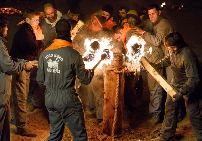 Met fakkels worden de toortsen aan de horens in brand gestoken.
