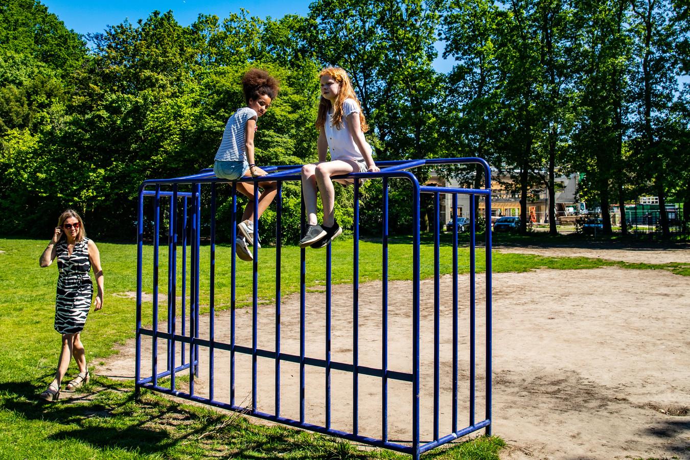 Cecile Wellen bekijkt hoe dochter Aimée Ahadji en haar vriendin Iris Hoogeslag op het voetbaldoeltje op het speelveld bij De Wingerd zijn geklommen