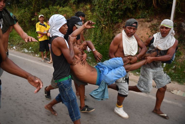 Aanhangers van de oppositieleider Guaidó dragen een gewonde aan de Braziliaanse kant van de grens.  Beeld AFP