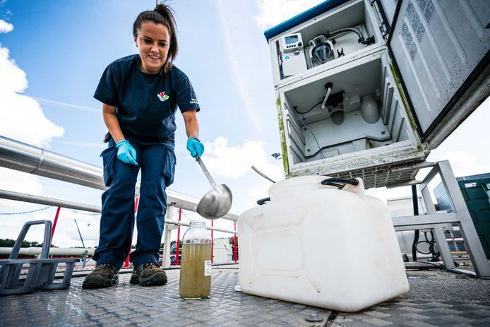 Een medewerker van de rioolwaterzuivering neemt een monster van het rioolwater. Het water wordt onderzocht op onder meer virusdeeltjes om zodoende te kunnen vaststellen hoeveel mensen het coronavirus onder de leden hebben en kunnen overdragen.