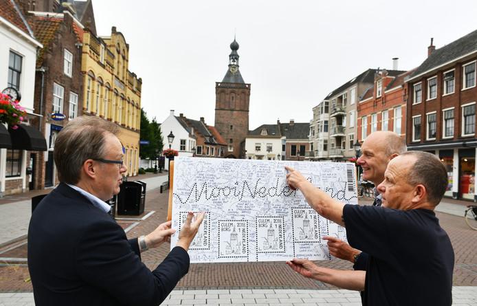 Presentatie van postzegel 700 jaar Culemborg. Van rechts naar links: Culemborger Ronald Puister, boekhandelaar Gerard Tomey en een medewerker van Post.nl.
