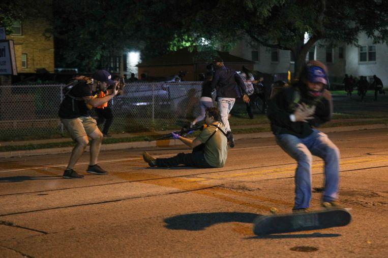 Kyle Rittenhouse, hier zittend op de grond, maakte dinsdagavond de straten van Kenosha onveilig met zijn AR-15. Beeld Anadolu Agency via Getty Images