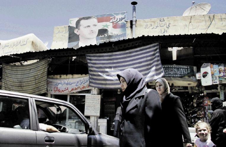 Op de markt in de oude stad van Damascus kijkt president Basjaar Assad over de menigte heen. (FOTO AP) Beeld AP