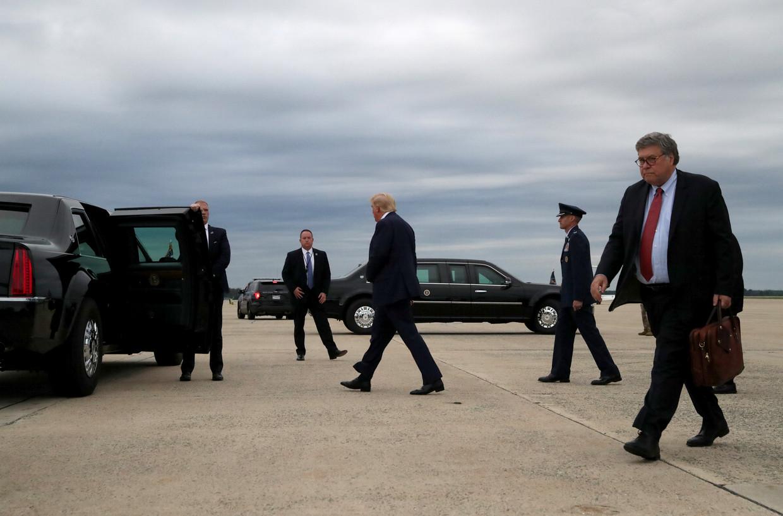 Bill Barr, minister van Justitie (met aktetas), en zijn baas Donald Trump lopen op een vliegveld in Maryland naar hun auto's. Barr werpt zich op als de handhaver van het trumpisme. Beeld Leah Millis / Reuters