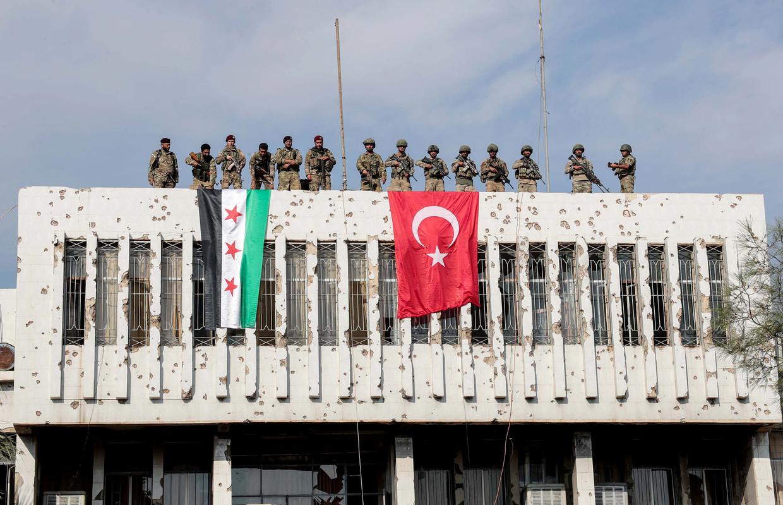Turkse militairen (rechts) en Syrische strijders die met hen meevechten op een gebouw in de grensplaats Ras al-Ain, waar ze de Koerden hebben verdreven. Beeld REUTERS