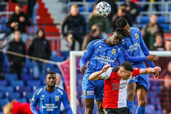 Vitesse met de oude sponsor. Idrissa Touré en Danilho Doekhi in duel met Feyenoorder Robert Bozenik, getooid in het shirt van een andere voormalige sponsor van de Arnhemse club.