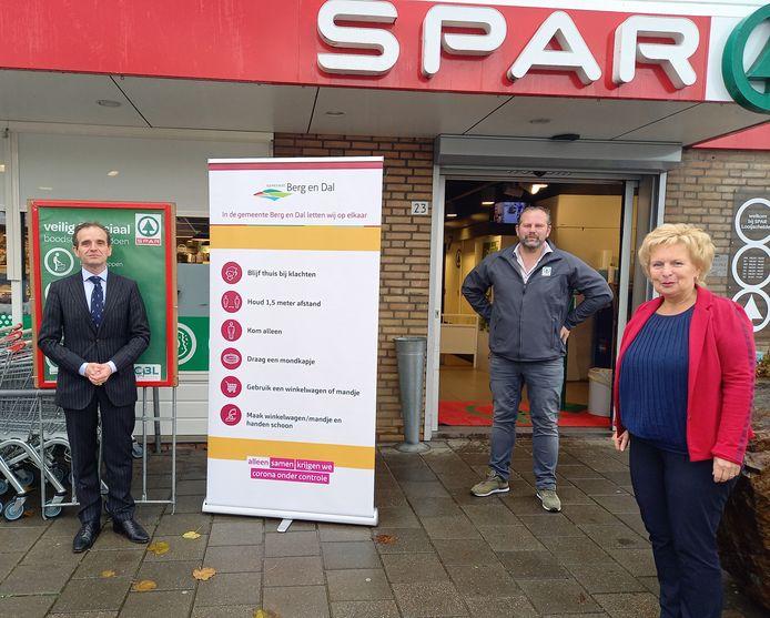 De eerste banner is neergezet bij de supermarkt in Ooij in bijzijn van burgemeester Mark Slinkman (l),  wethouder Irma van de Scheur en Peter Looijschelder van de Spar.