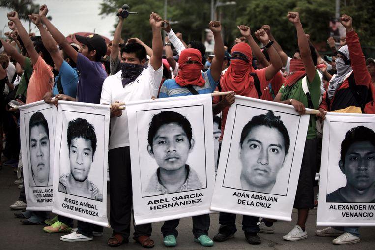 Studenten van de lerarenopleiding met foto's van hun verdwenen medestudenten tijdens een demonstratie in Acapulco. Beeld Felix Marquez
