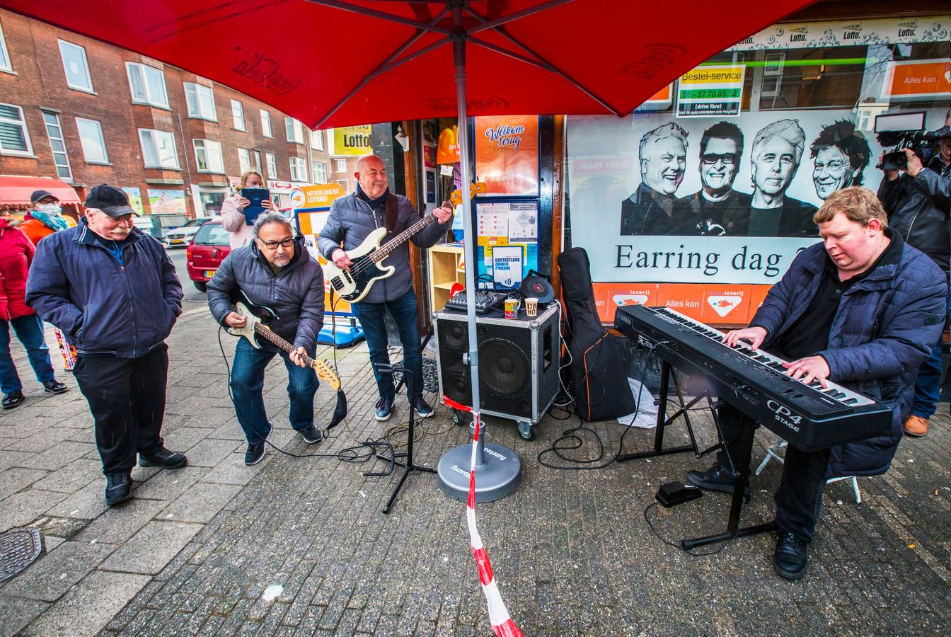 Ron Lezer (Gitaar), Willem Augesteijn (Bas) en Patrick Lejewaan (toetsen) spelen het Golden Earringnummer Radar Love in de Terletstraat voor het Prijspaleis. Rooie Ruud (met pet) kijkt toe.