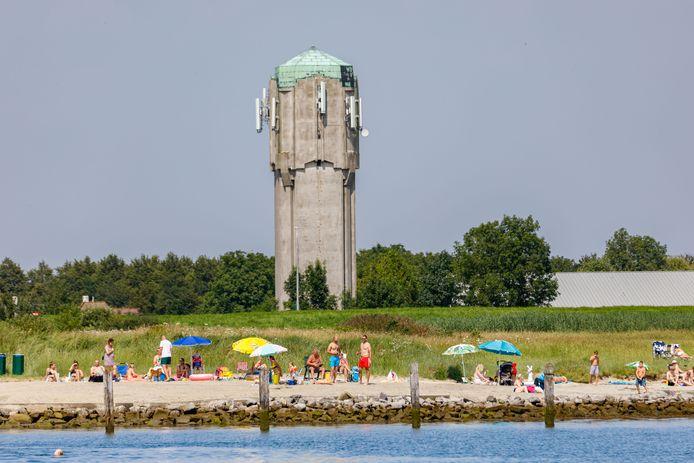 Het populaire strandje bij de haven van Sint Philipsland met de op de achtergrond de met groen begroeide oude vuilstort.