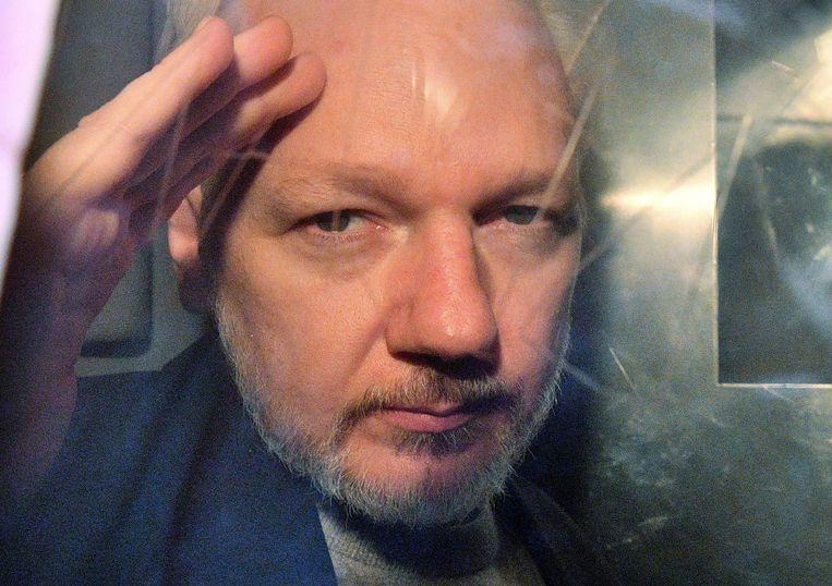WikiLeaks-oprichter Julian Assange maakte in mei van dit jaar gebaren vanuit het raam van een gevangenisbusje. Beeld AFP