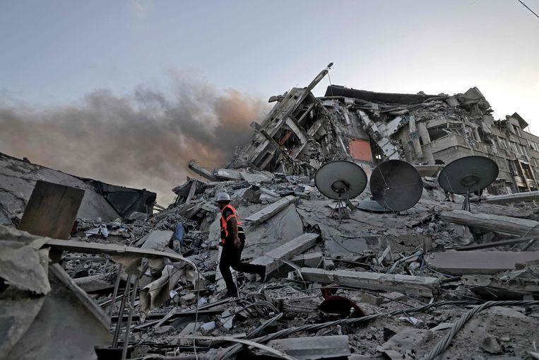 In Gaza-Stad zijn woensdag zeker twee flatgebouwen ingestort en talloze auto's in brand gevlogen. Beeld AFP