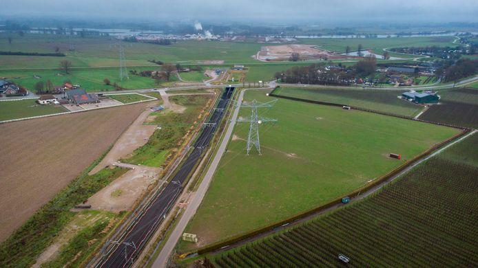De tunnelbak voor de Betuweroute, met daarachter eerst de dijk en daarna het Pannerdensch Kanaal. De door te trekken A15 komt links daarvan - iets eerder heeft die het spoor van zuid naar noord gekruist - op een talud te liggen, om met een brug de rivier over te steken.