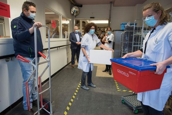 Ziekenhuis Rivierenland neemt de eerste coronavaccins in ontvangst; rechts met de rode koelbox in de hand Katinka Molenaar en midden met de witte doos Ella Spijkerman.