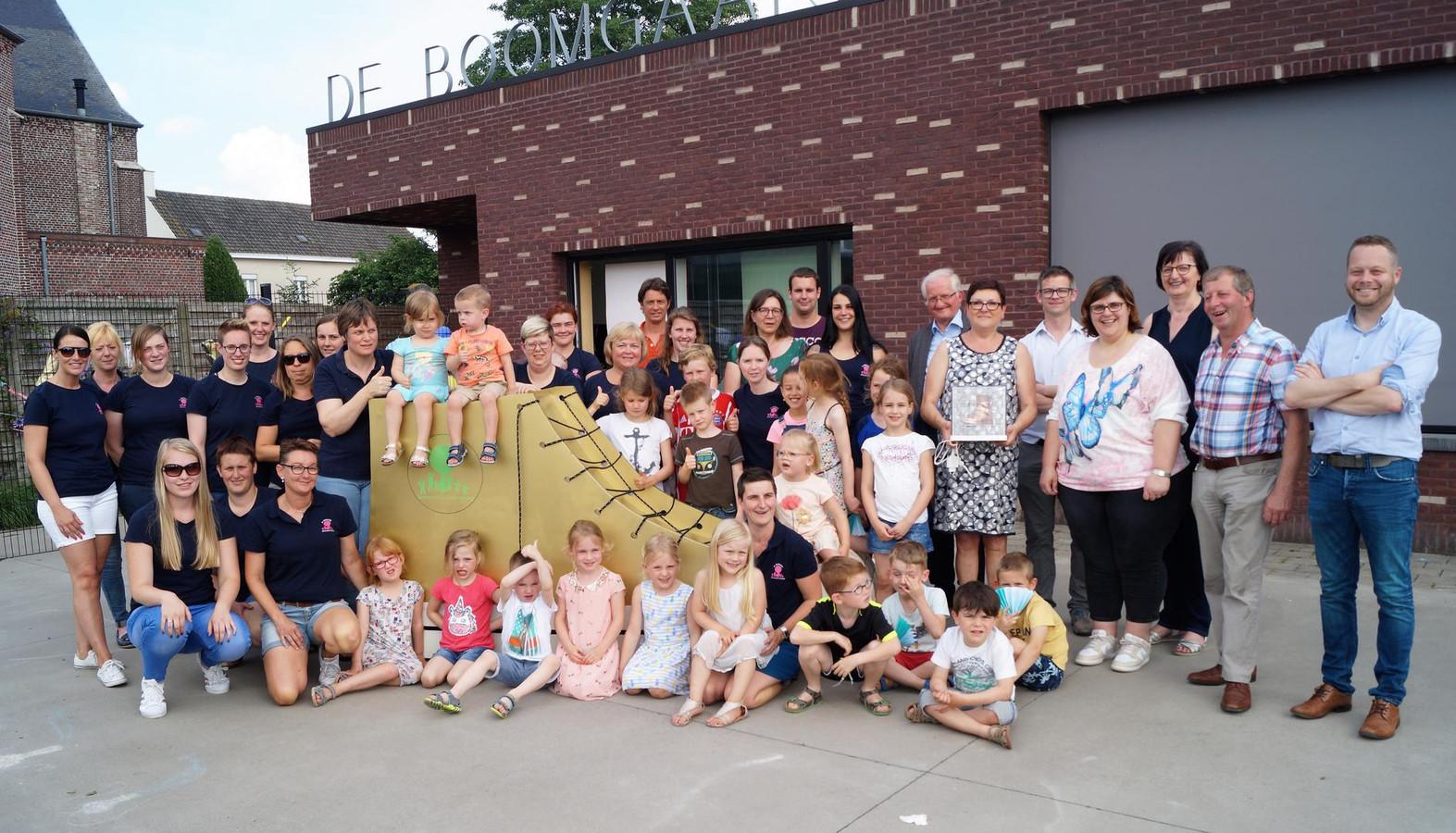 De medewerkers, ouders en kinderen van kinderopvang De Boomgaard bij de reuzenkinderschoen.