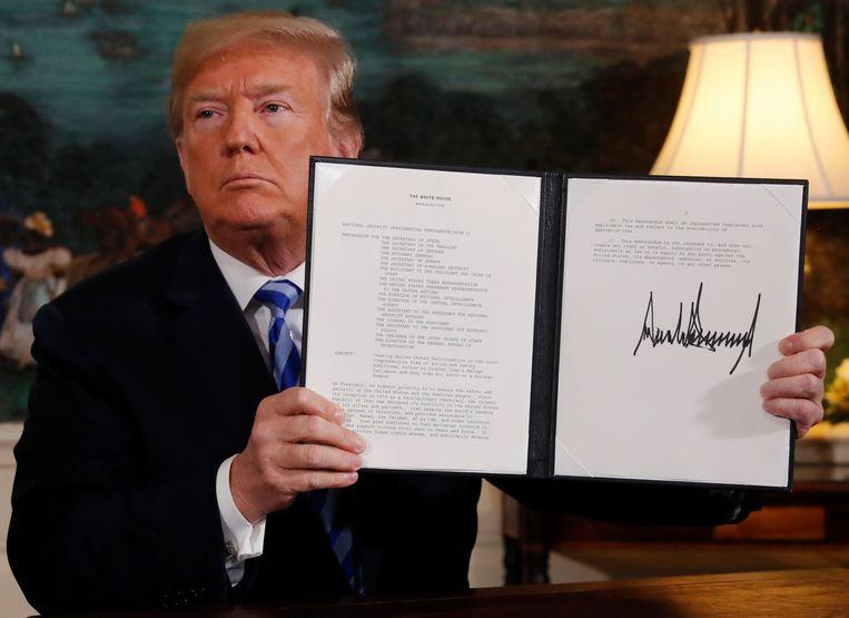 Donald Trump ondertekent het presidentieel besluit waarbij de Verenigde Staten zich officieel uit het Iran-akkoord terugtrekken. Beeld REUTERS