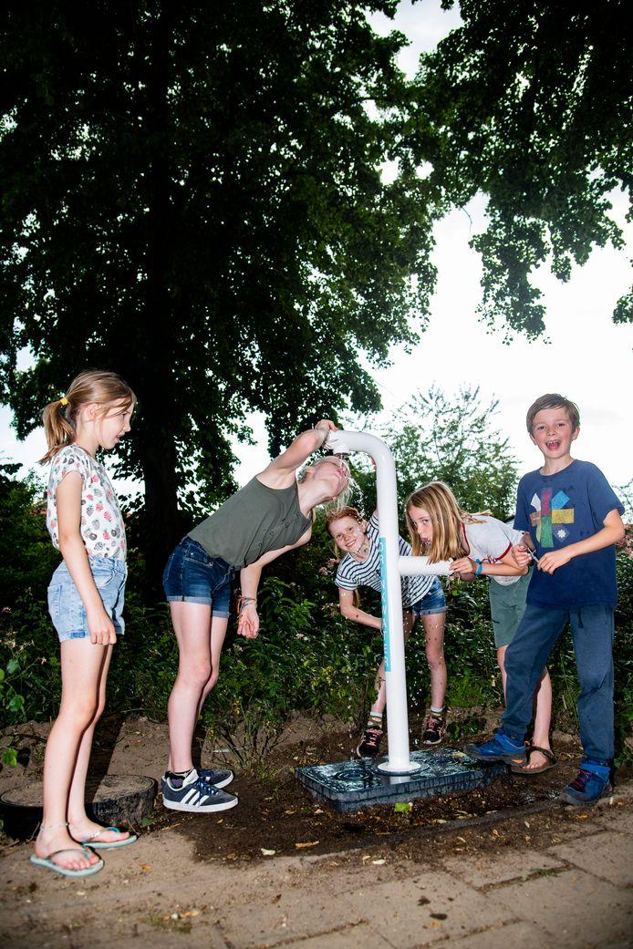 Noor, Hanna, Josien, Lucie en Lennart (vlnr) genieten van de waterkraan.