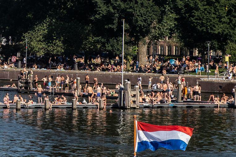 Mensen genieten van het zomerse weer op het Marineterrein in Amsterdam.  Beeld Joris Van Gennip