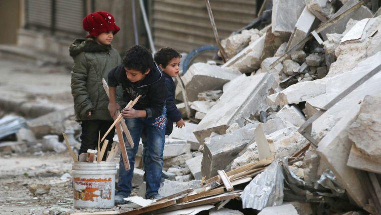 Kinderen sprokkelen brandhout in de puinhopen van een pand dat is verwoest bij bombardementen. Beeld reuters