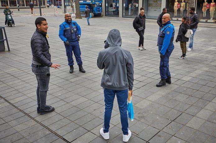 Handhavers Salah Lagritite (links) en Nees Botokat van Stadstoezicht in het centrum rond de Lijnbaan. Ze spreken groepen aan en kijken of mensen anderhalve meter afstand houden.