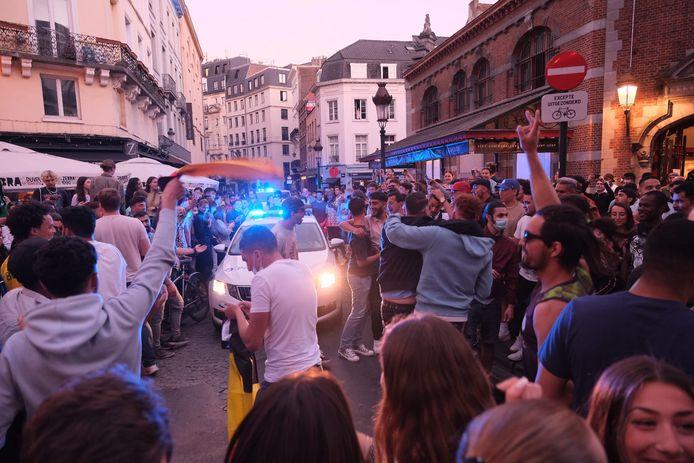 De politie wurmt zich met wagen en zwaailicht doorheen de menigte.
