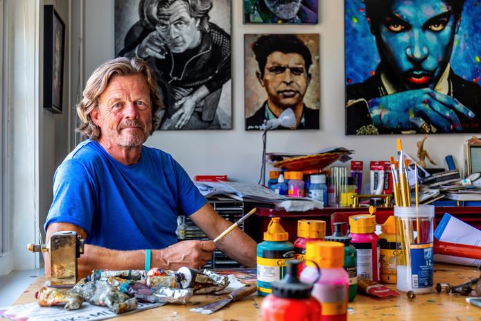 De Utrechtse kunstenaar John Noy in zijn atelier, achter hem hangt een zelfportret. Rechts een portret van popartiest Prince.
