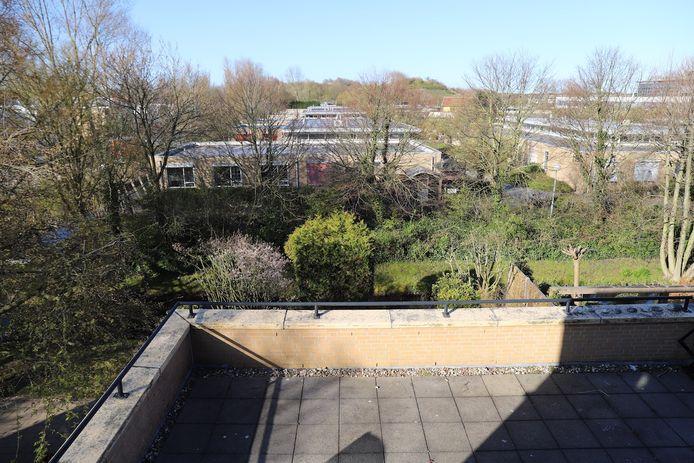 Het uitzicht van de bewoners vanaf het dakterras van de woningen in de winter. Achter de bomen liggen de units. Op de achtergrond zie je de duinen.