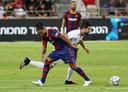 Een lachende Ronaldinho in duel met Rubén de la Red.