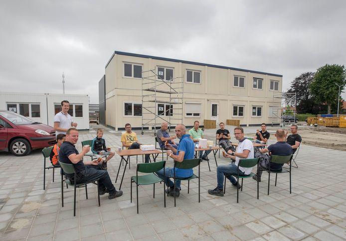 Vaders van de Julianaschool in Krabbendijke namen zaterdag tussen het harde werken door even een korte pauze bij het tijdelijke onderkomen van de school.