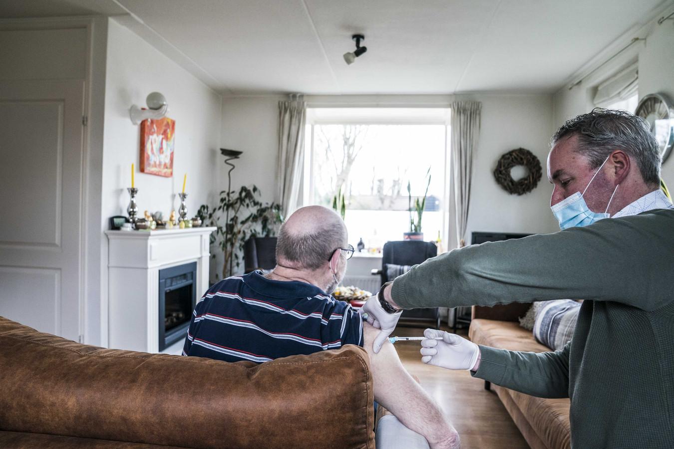 Een huisarts vaccineert een man tegen het coronavirus.