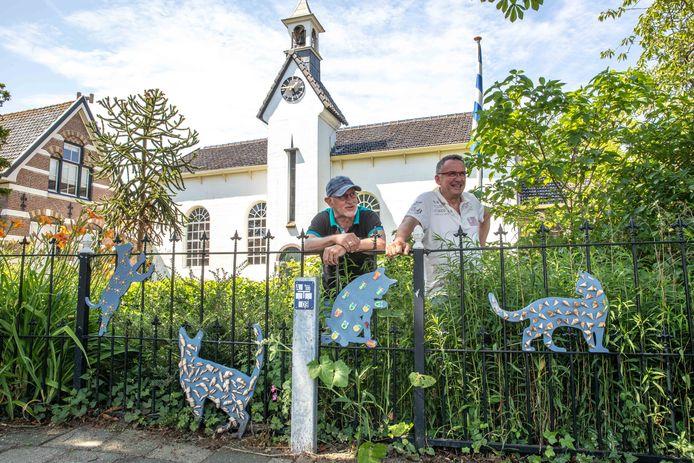 Twee van de drie organisatoren van de Zomerstart Kats: Chris van der Kraan (links) en Frans Borggreve. Op de achtergrond de Katse Kerk, waar de opbrengst van de houten kattenverkoop naartoe gaat.