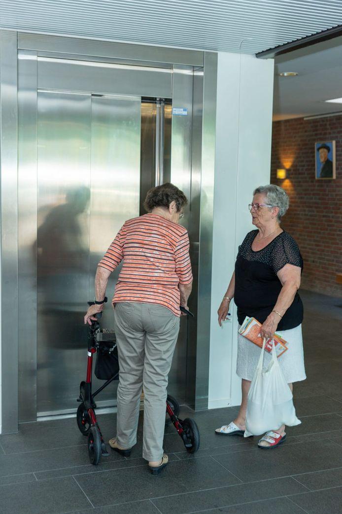 Lenie Burger (rechts) kan eindelijk weer met de lift naar boven. Haar buurvrouw (links) heeft een volle week vast gezeten op haar eigen etage.