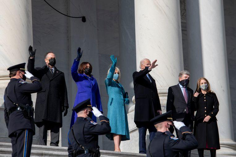 Doug Emhoff (links) zwaait vóór de inauguratie-ceremonie samen met echtgenote Kamala Harris, Jill Biden en Joe Biden naar het publiek bij het Capitool.  Beeld AP
