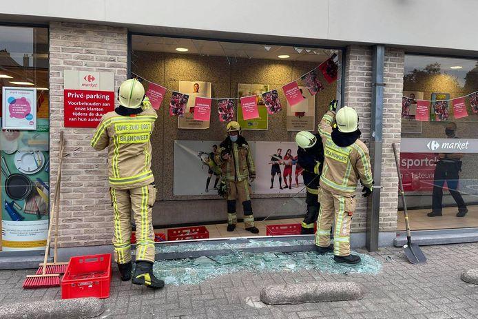Vrijwilligers van brandweerpost Lede timmerden met houten platen het stuk gereden vensterraam op de parking van Carrefour dicht.