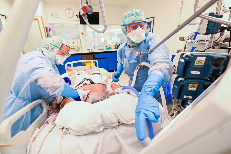 Medisch personeel verzorgt een coronapatiënt in een ziekenhuis in Aarlen. Beeld Photo News