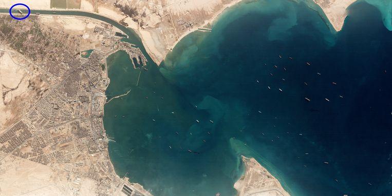 Een satellietbeeld toont helemaal linksboven de vastgelopen Ever Given, en tientallen andere schepen die liggen te wachten voor de ingang van het kanaal. Beeld via REUTERS