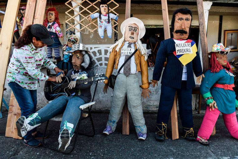 Oudejaarspoppen te koop in het Colombiaanse Rionegro. De poppen (zoals rechts de Venezolaanse president Nicolas Maduro) worden oudejaarsnacht verbrand. Beeld AFP