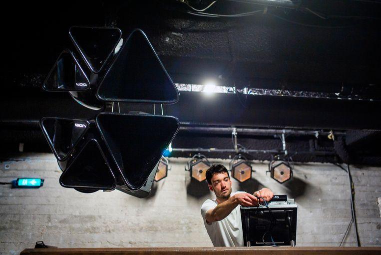 Jort Vrijsen, een van de drie eigenaren van club Basis, installeert dj-apparatuur. Beeld Jiri Büller / de Volkskrant