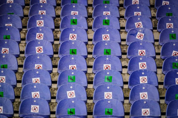 Lege stoelen met stickers in een voetbalstadion. Foto ter illustratie.