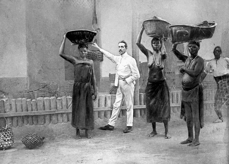 Inheemse arbeiders en een witte chef in de Onafhankelijke Congostaat, 1899.  Beeld Hollandse Hoogte / Sueddeutsche Zeitung Photo
