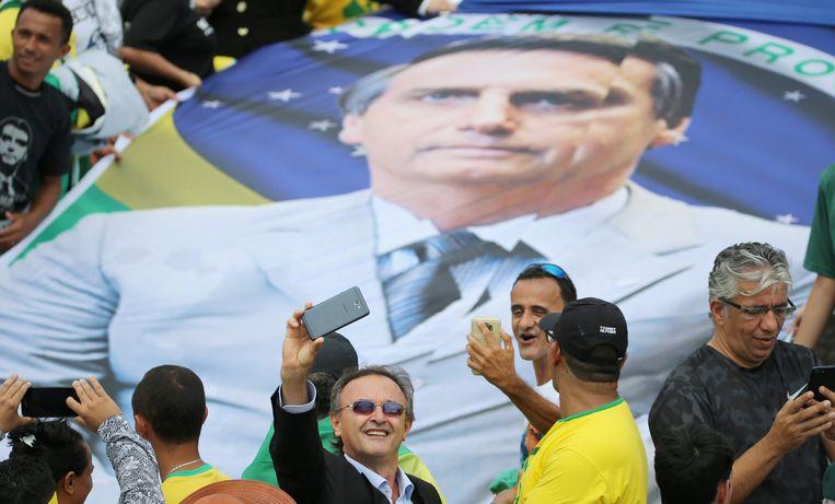 Aanhangers van de nieuwe Braziliaanse president maken selfies bij zijn portret tijdens het wachten op de inauguratie voor het Planalto-paleis in de hoofdstad Brasilia. Beeld REUTERS