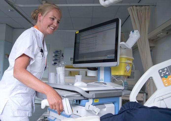 Een verpleegkundige scant de streepjescode op de polsband van een patiënt alvorens hem medicijnen toe te dienen.
