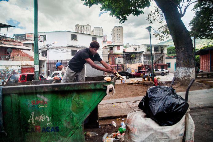 Twee mannen zoeken tussen het vuil of ze iets bruikbaars of te eten kunnen vinden. Vanwege de crisis kunnen veel mensen zich niet voldoende voorzien in hun dagelijkse levensbehoeften.