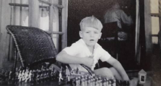 Theo Doorman speelt met tinnen soldaatjes in hun huis in Soerabaja, 1941. Op de achtergrond is vader Karel aan het werk.