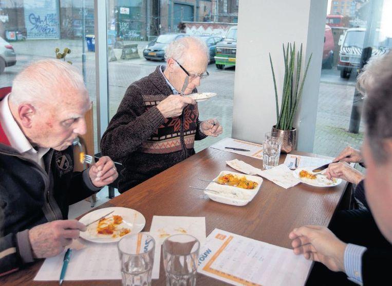 Leden van de Trouw Tafeltje-dek-je Test proeven de diepvriesmaaltijden. 'Als ik niet meer zelf kan koken, zou ik liever kiezen voor een verantwoorde broodmaaltijd.' Beeld Maartje Geels