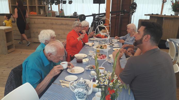 Ouderen genieten van de high tea.