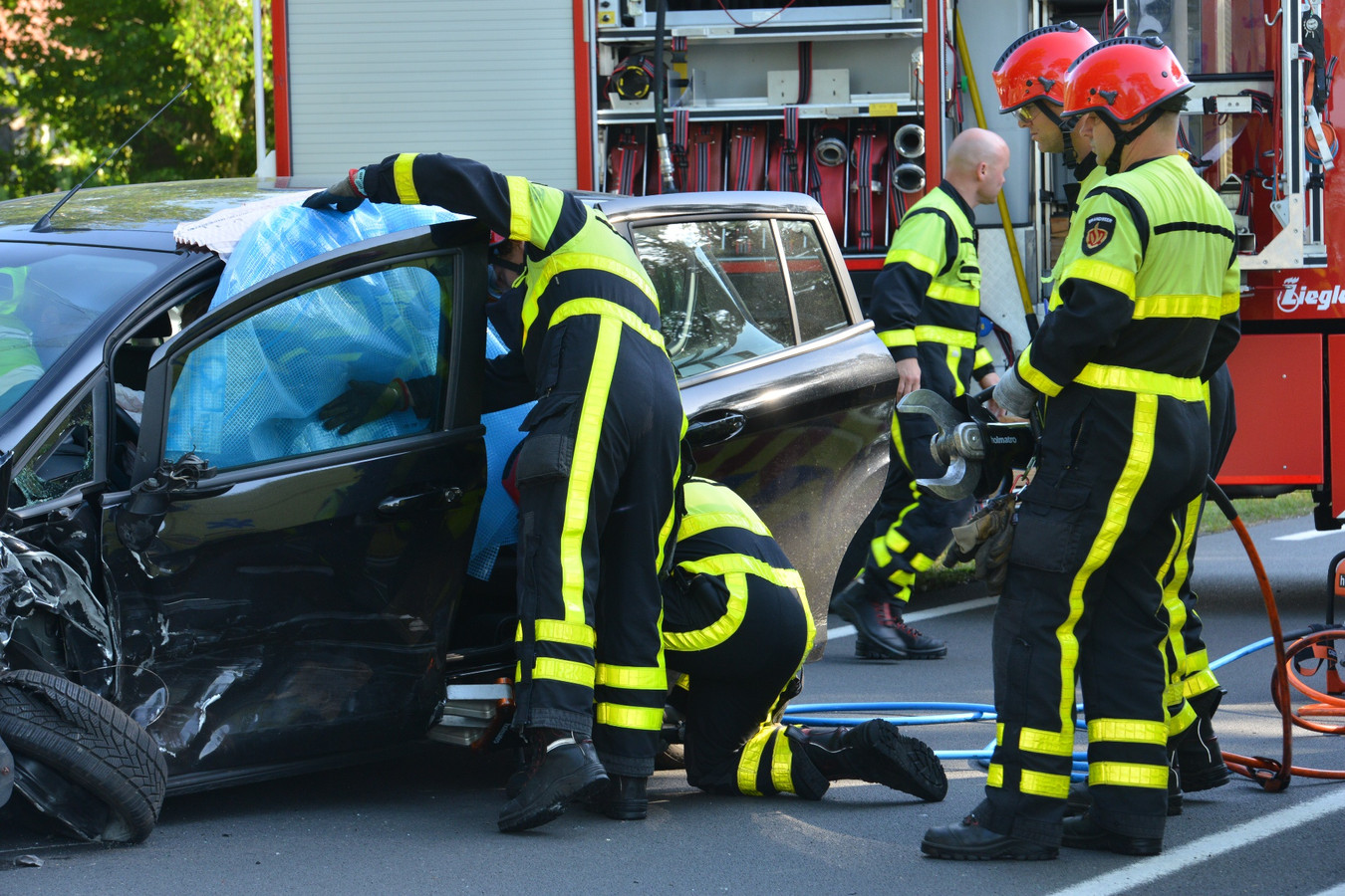 De brandweer bevrijdt de beknelde vrouw uit haar auto in Breda.