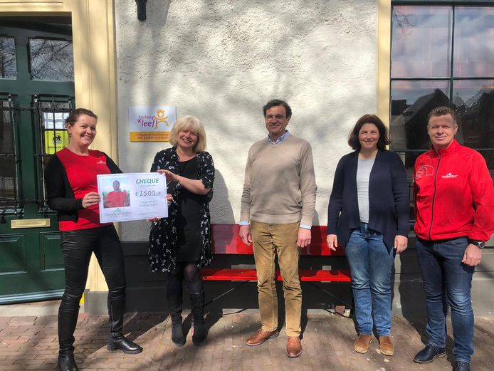 De leden van de hardloopclub Trim overhandigen de stichting 'kLEEF! een cheque van 1500 euro, een actie voor de ernstig zieke Timo uit Apeldoorn
