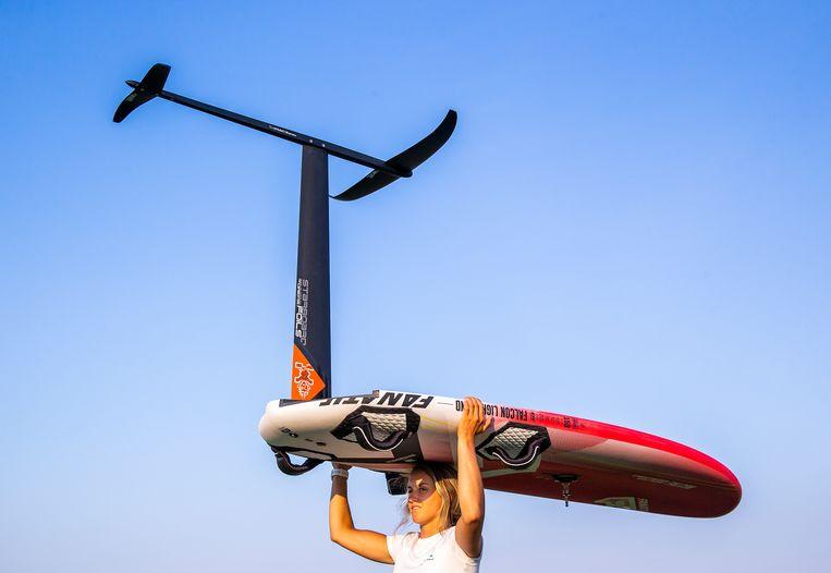 Lilian de Geus draagt haar Foiling Surfplank naar het water, eind mei in Medemblik. Surfen op een foil vergt een geheel andere techniek dan het 'klassieke surfen'.     Beeld Jiri Buller